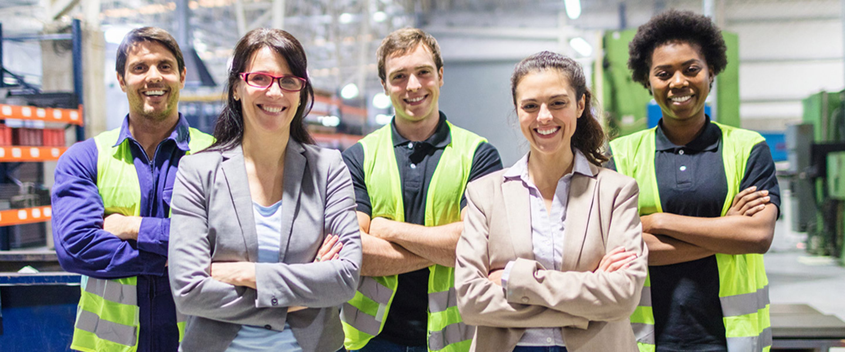 Two business women and three warehouse workers wearing safety vests smile in factory warehouse
