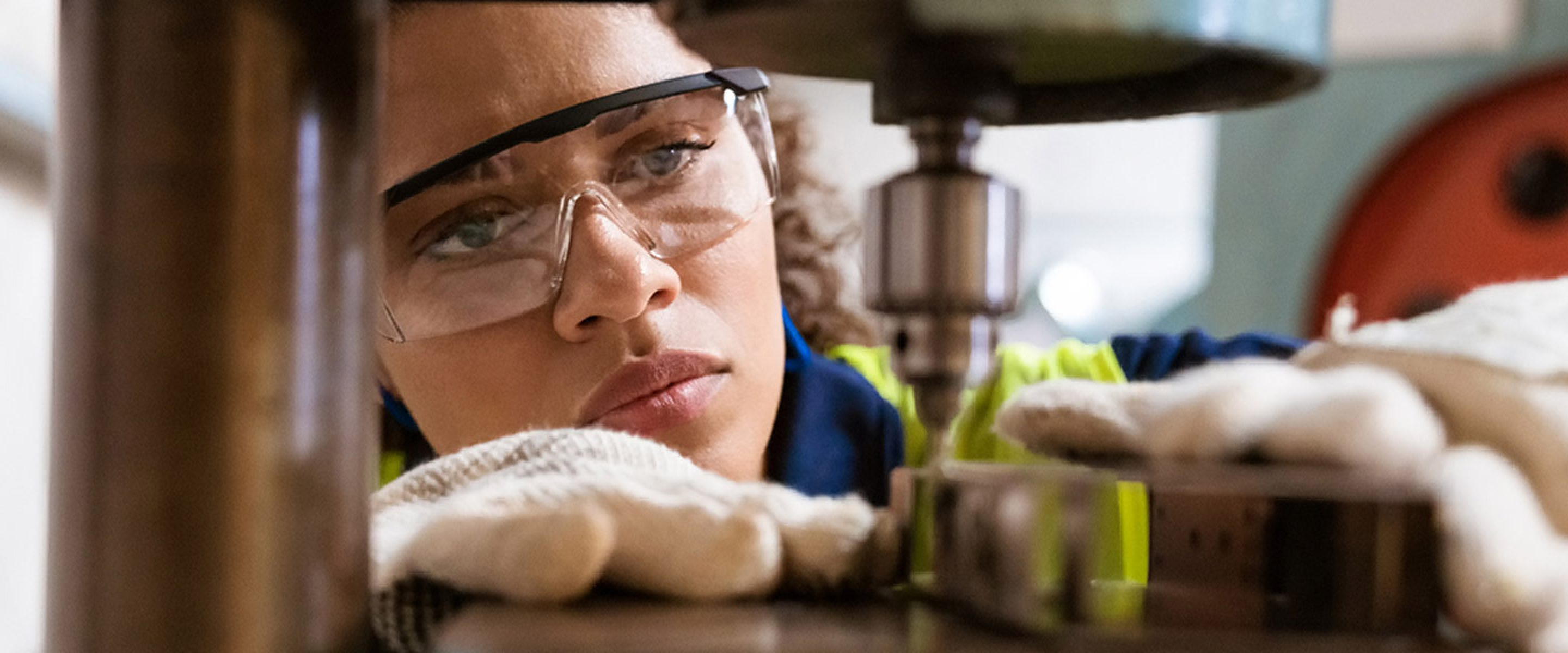 Closeup of female worker wearing safety glasses and working on a machine