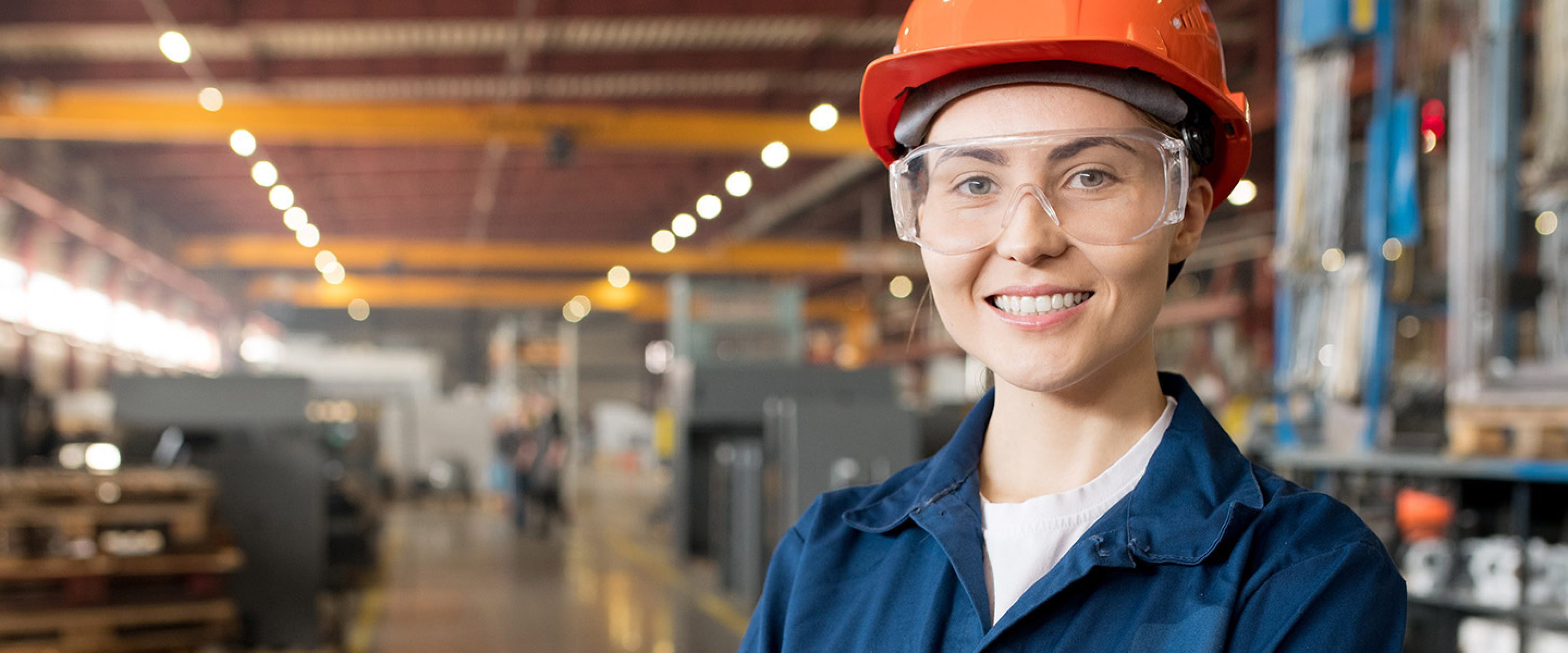 Young female worker wearing safety glasses and a hard hat smiles in a factory